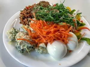 Salat mit Eier, Reis und Gemüse wie Broccoli, Rübe und Paprika mit Ruccola-Sesame Topping auf weißem Teller im Nahaufnahme