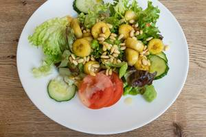 Salat mit Eisbergsalat, Tomate, Gurke, flambierte Banane und Pinienkerne