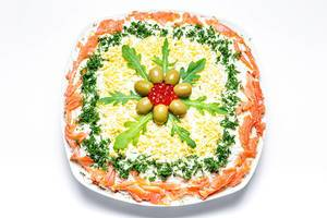 Salat mit Gemüse und Lachs verziert mit Kräutern, Rucolablättern, Oliven und rotem Kaviar vor weißem Hintergrund Draufsicht