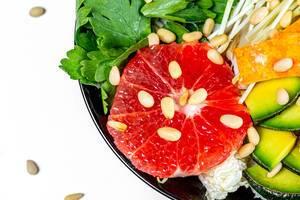 Salat mit Grapefruit-Scheibe, Avocado, Mikrogrün, Petersilie und Pinienkernen als gesundes Essen Nahaufnahme