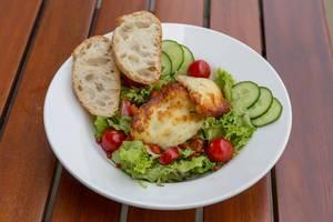 Salat mit Gurken, Cherrytomaten, Haloumi-Käse und zwei Scheiben Brot