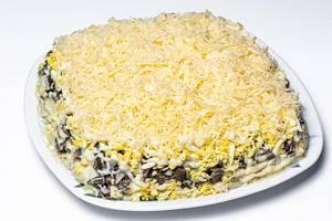 Salat mit Hähnchen, Gemüse, Käse und Pilzen auf einem Teller auf weißem Hintergrund