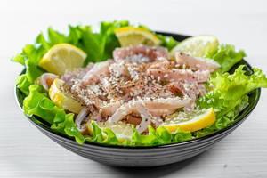 Salat mit Meeresfrüchten und Sesam in einer schwarzen Schüssel, auf einem weißen Tisch