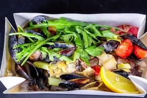 Salat mit Muscheln, Zitrone, Tomaten und Rucola in Kartonbox