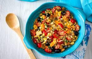 Salat mit Quinoa, schwarzen Oliven, Cherrytomaten, Paprika und Mais. Draufsicht