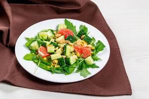 Salat mit Rucola, Gurken, Grapefruit und Nüssen auf einem weißen Teller