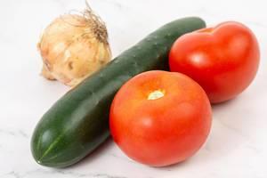 Salatzutaten wie eine Gurke mit Schale, Tomaten und eine Zwiebel, auf einer marmorierten Oberfläche