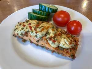 Salmon filet with topping, fresh herbs, tomatoes and cucumber on a white plate in Berlin-Köpenick, Pentahotel