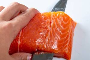 Salmon fillet is cut with a knife. Close up