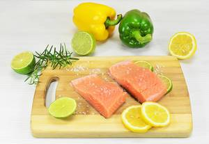 Salmon Fillet on a Wooden Cutting Board with Lemon and Salt