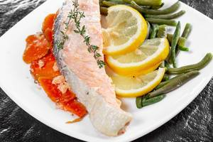 Salmon with vegetables thyme and lemon slices close up (Flip 2019)