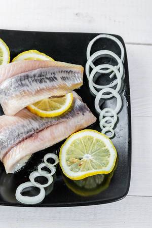 Salted herring with onion rings and lemon circles