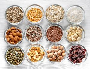 Samen, Nüsse, Körner in Glasschalen aus der Sicht von oben, auf einem weißen Holztisch
