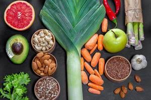 Sammlung von gesunden Zutaten für ein ausgewogenes Mittagessen, auf einem schwarzen Tisch