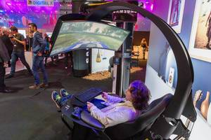 Samsung Gaming Mann sitzt in einem Gaming Stuhl mit einem Curved Fernseher vor ihm