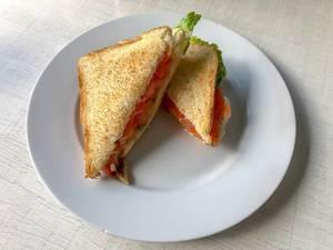 Sandwich-Ecken mit geräuchtertem Lachs, Tomate und Salat auf einem weißen Teller