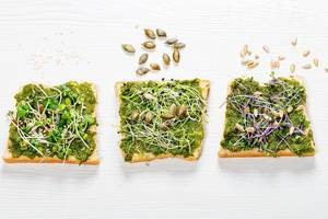 Sandwich with herbs, micro greens and seeds on white wooden background (Flip 2019)
