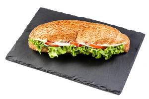 Sandwich with lettuce cheese ham and tomato on black stone tray (Flip 2019)