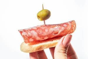 Sandwich with salami and green olive in a woman