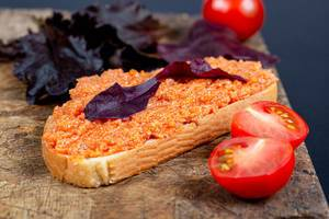 Sandwich with zucchini caviar and purple lettuce leaves on an old kitchen board with fresh tomatoes