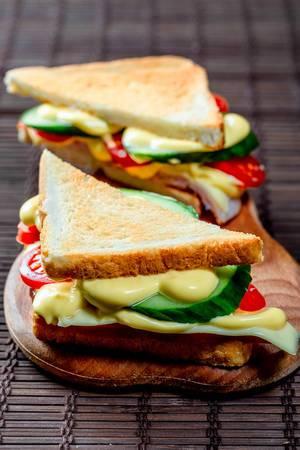 Sandwiches dreieckig mit Schinkenkäsetomaten-Salat und geröstetem Brot