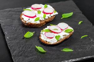 Sandwiches with cheese, radish slices and Basil leaves on a black background (Flip 2019)