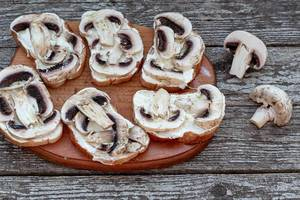 Sandwiches with mushrooms before baking on an old wooden background. The view from the top