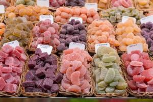 Saure Drops und farbenfrohe spanische Süßigkeiten in Holzkörben am Marktstand im Mercat de la Boqueria, Barcelona