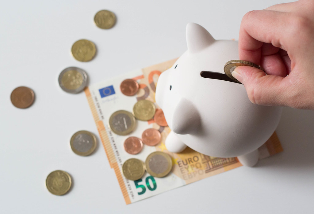 Saving money - cash in euroes with a piggybank