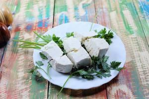 Schafkäse und Petersilie auf einem weißen Teller mit Salz- und Pfefferstreuer auf einem bunten Tisch im Country-Stil
