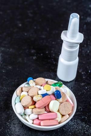 Schale mit farbigen Pillen und Tabletten neben Nasenspray bei Erkältung vor schwarzem Hintergrund