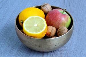 Schale mit Nüssen, Zitrone und Apfel