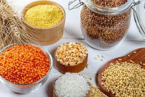 Schalen mit verschiedenen Getreidesorten wie Reis, Hirse, Linsen, Erbsen und Buchweizen