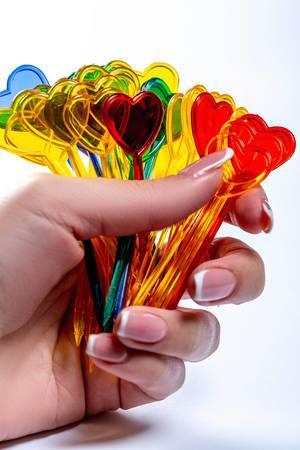 Scharfe mehrfarbige Plastikspieße mit Spitzenherzen in der Hand einer Frau