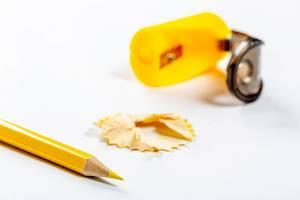 Scharfer gelber Buntstift vor einem Spitzer, auf einem weißen Tisch