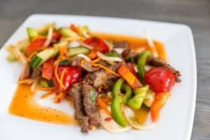 Scharfes thailändisches Essen mit Rindfleisch, gesundem Gemüse, Zwiebeln, Karotten und Fischsuppe auf einem Holztisch in der Nahaufnahme