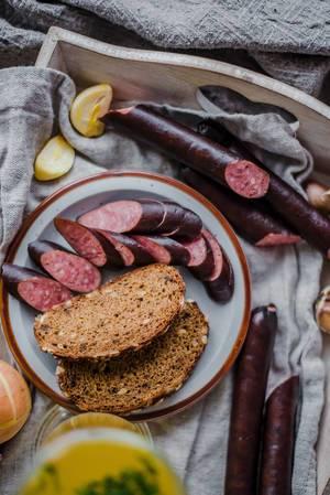 Scheiben dunkles Brot mit Wurst und Knoblauch angerichtet auf Holztablett