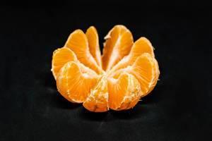 Scheiben einer Mandarine vor schwarzem Hintergrund