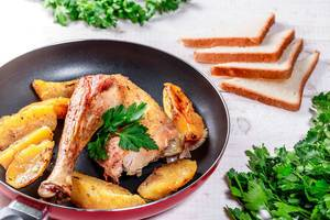 Scheiben von Bratkartoffeln mit Huhn in einer Pfanne