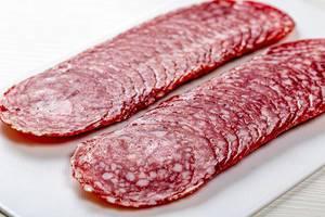 Scheiben von geräucherter Salamiwurst, auf weißem Küchenbrettchen