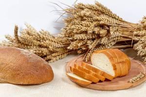 Scheiben Weißbrot und ein Rogenbrot mit Weizenähren auf weißem Hintergrund