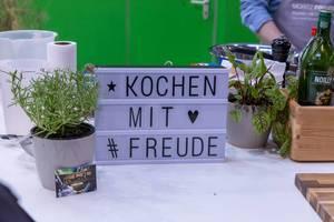 Schild mit Aufschrift Kochen mit Freude zwischen Gartenkräutern und Gewürzen