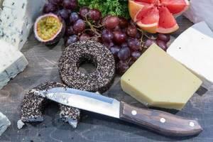 Schimmelkäse, Frischkäse und Hartkäse liegt mit einem Messer auf einer Holzoberfläche neben frischem Obst