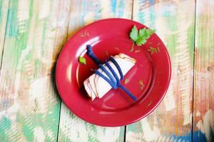 Schinken mit einem Band umwickelt, auf einem roten Teller