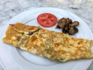 Schinken-Pilz Omelette mit Pilzen und einer Scheibe Tomaten auf einem weißen Teller