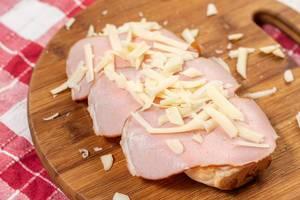 Schinkenscheiben und geriebener aromatischer Käse auf Brötchen auf hölzernem Küchenbrett