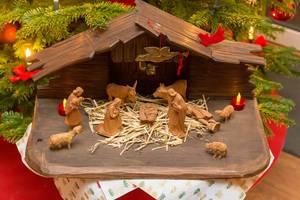 Schlichtes Krippenspiel mit geschnitzten Holzfiguren vor Weihnachtsbaum
