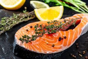 Schließen Sie oben vom rohen Lachs mit frischen Thymian- und Zitronenscheiben