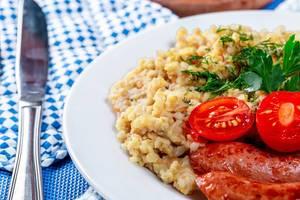 Schließen Sie oben vom Weizenbrei mit Würsten auf einer weißen Platte