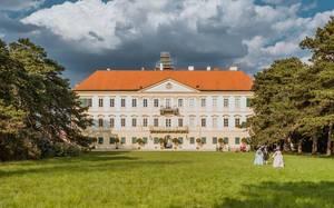 Schloss Feldsberg mit Bäumen, bewölktem Himmel und Besuchern in Barockkleidung, in Valtice, Tschechien